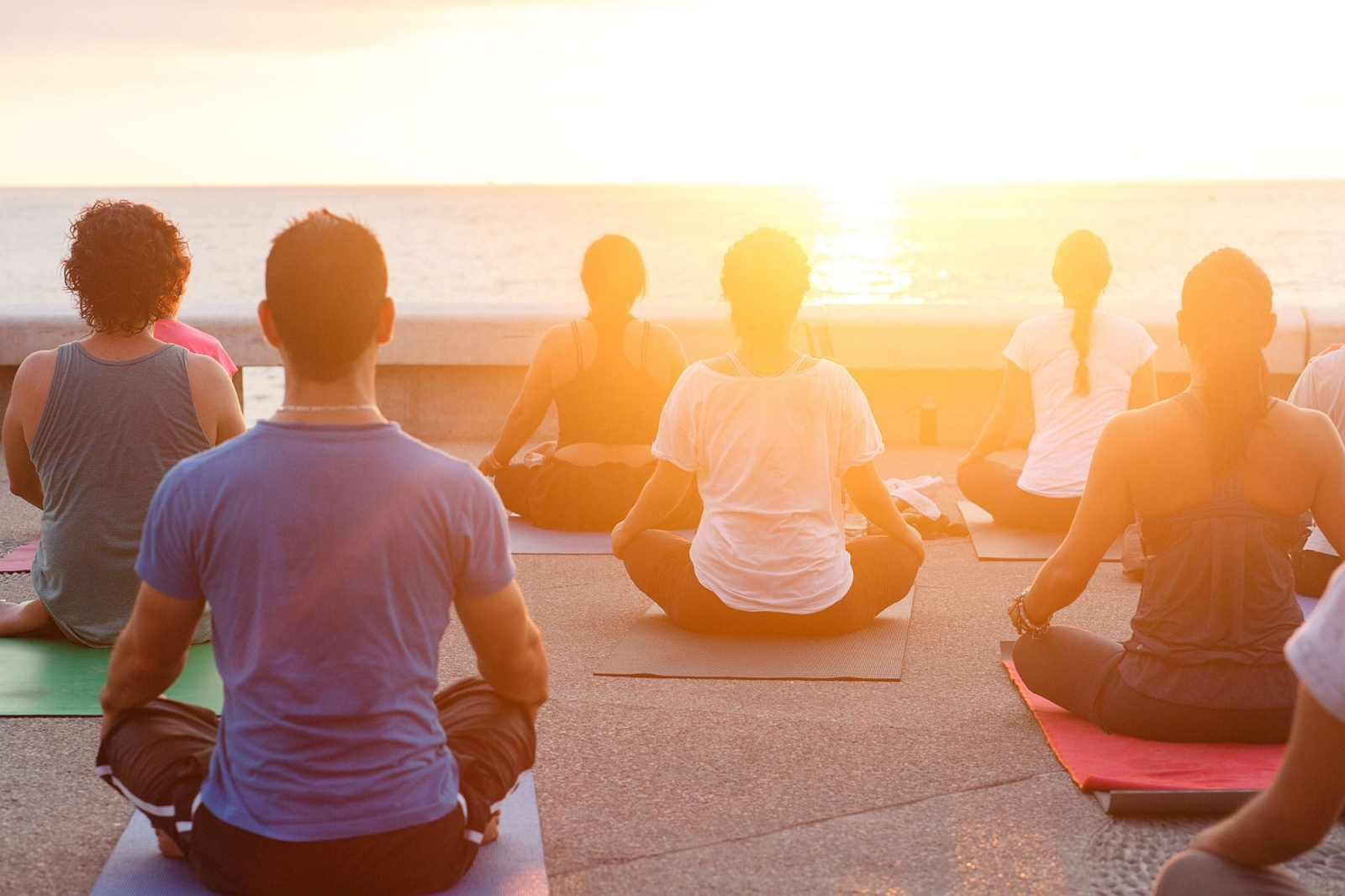 photo of people meditating while looking towards the sun